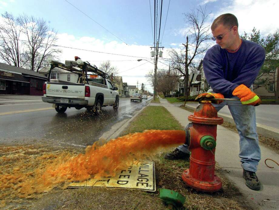 A water company operator opens a valve to purge a fire plug of rusty water. Photo: File Photo / THE SCHENECTADY DAILY GAZETTE