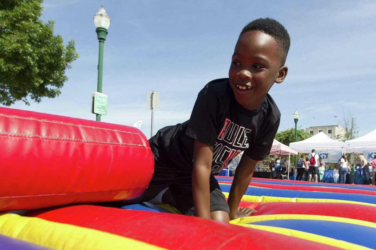Kahiden George, right, laughs is knocked down off a podium as he plays game during the annual KidzFest in downtown Conroe, Saturday, April 28, 2018. This year's event is Saturday, April 27.