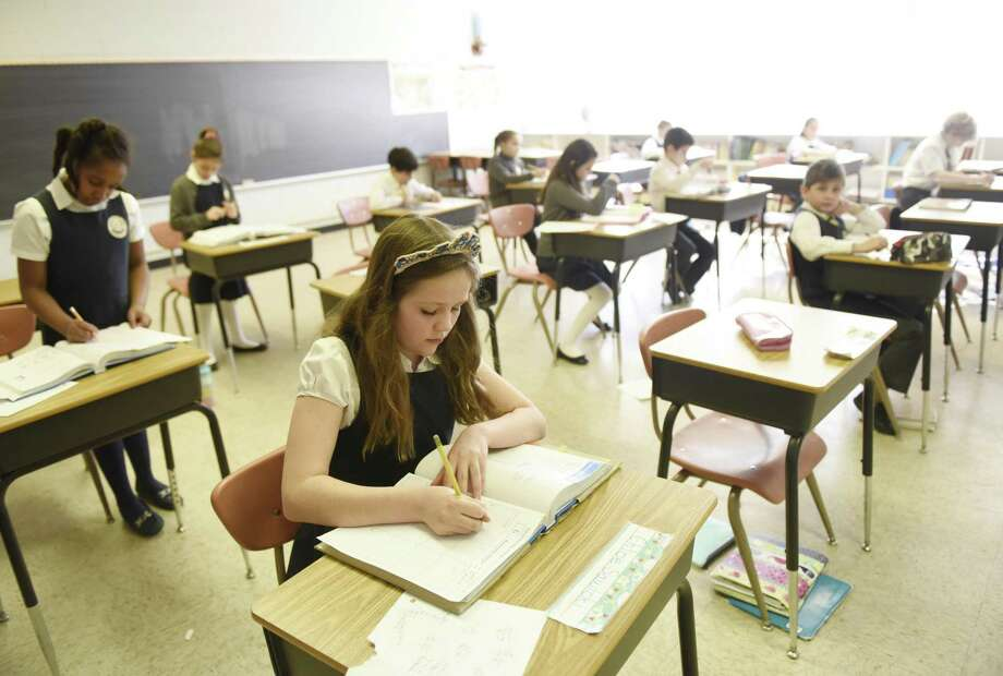 Students attend school at Regina Pacis Academy in Norwalk, Conn. Wednesday, March 6, 2019. Regina Pacis Academy is a K-8 Catholic classical school independent of the Diocese of Bridgeport Catholic Schools. As diocesan schools move toward models similar to public and private schools, many Catholic families are choosing schools like Regina Pacis, which reject technology, common core curriculum and put Catholic formation at the center of the classroom. Photo: Tyler Sizemore / Hearst Connecticut Media / Greenwich Time