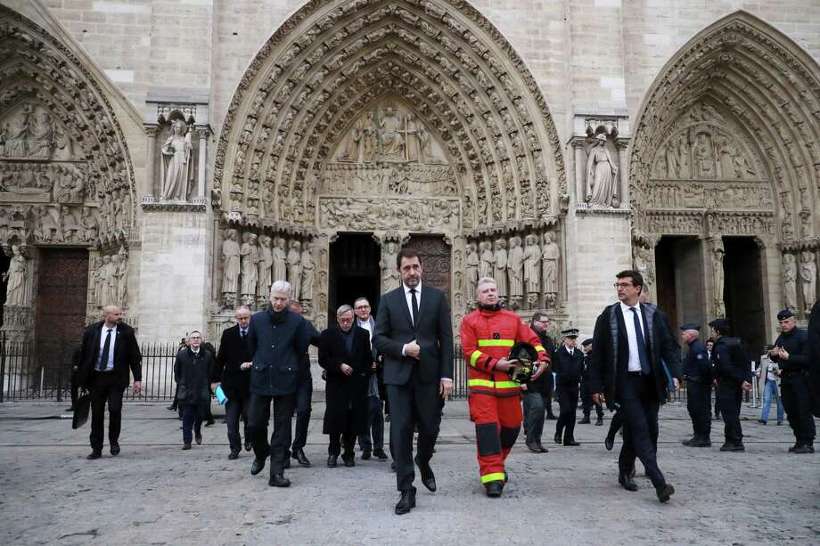 French Interior Minister Christophe Castaner, center,leaves after visiting Notre Dame cathedral in Paris, Tuesday, April 16, 2019. Firefighters declared success Tuesday in a more than 12-hour battle to extinguish an inferno engulfing Paris' iconic Notre Dame cathedral that claimed its spire and roof, but spared its bell towers and the purported Crown of Christ. (Christophe Petit Tesson, Pool via AP) Photo: Christophe Petit Tesson / Associated Press / EPA POOL