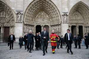 French Interior Minister Christophe Castaner, center,leaves after visiting Notre Dame cathedral in Paris, Tuesday, April 16, 2019. Firefighters declared success Tuesday in a more than 12-hour battle to extinguish an inferno engulfing Paris' iconic Notre Dame cathedral that claimed its spire and roof, but spared its bell towers and the purported Crown of Christ. (Christophe Petit Tesson, Pool via AP)