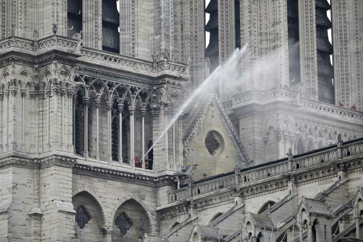Firefighters spray water on the roof of Notre Dame cathedral after the fire in Paris, Tuesday, April 16, 2019. Experts are assessing the blackened shell of Paris' iconic Notre Dame cathedral to establish next steps to save what remains after a devastating fire destroyed much of the almost 900-year-old building. With the fire that broke out Monday evening and quickly consumed the cathedral now under control, attention is turning to ensuring the structural integrity of the remaining building. (AP Photo/Kamil Zihnioglu)