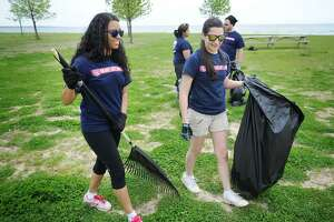 File photo showing then-Fairfield University seniors Pauline Santos, left, and Camile Gomes, clean up Seaside Park in Bridgeport Conn. on Tuesday, May 13, 2014.