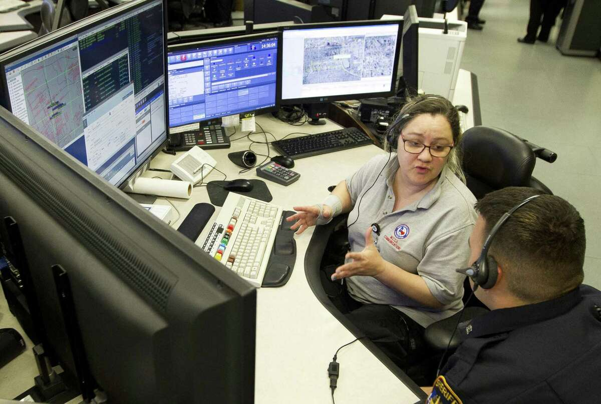 Dispatcher Kimberly McCarty explains her job to an officer with the Montgomery County Sheriff's Office, Tuesday, April 9, 2019, in Conroe.