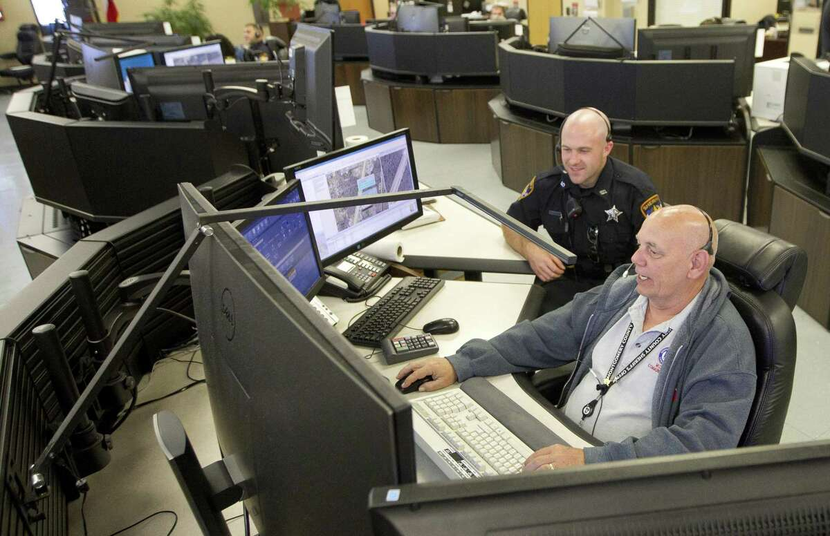 A dispatcher shows an officer with the Montgomery County Sheriff's Office how he handles a call, Tuesday, April 9, 2019, in Conroe.