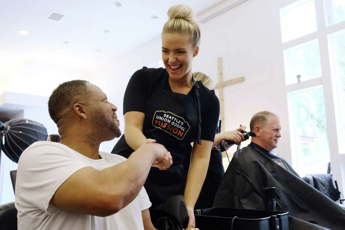 Jen (Jo) Mortensen, of Gene Juarez, shakes hands with Sedrick after cutting his hair, Tuesday, at an event at the Union Gospel Mission in Burien, where 50 homeless men in recovery are getting makeovers this week, April 16, 2019. (Genna Martin, Seattlepi.com)