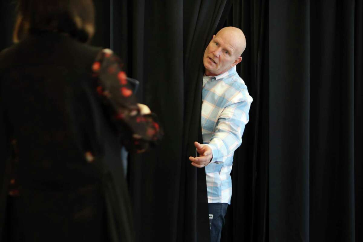 Scott Cain reaches out of the dressing while trying on outfits, Tuesday, at an event at the Union Gospel Mission in Burien, where 50 homeless men in recovery are getting makeovers this week, April 16, 2019. (Genna Martin, Seattlepi.com)