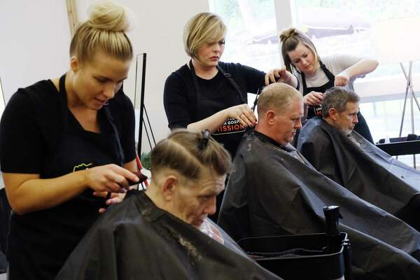 Hair stylists (from left) Elizabeth Tiniakoff, Amanda Lufkin and Jen (Jo) Mortenson give free haircuts to Ralph, Scott and Bill during an event hosted by the Union Gospel Mission in Burien, where 50 homeless men in recovery are getting makeovers this week, Tuesday, April 16, 2019. (Genna Martin, Seattlepi.com)