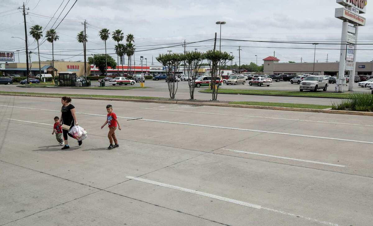 Elizabeth Anaya and her two children, Alexander, left, and Benjamin, right, cross Hillcroft Avenue near Bellaire Boulevard after leaving a Fiesta grocery store on April 16 in Houston. Anaya lives near the store, and said it's very dangerous to cross the street.