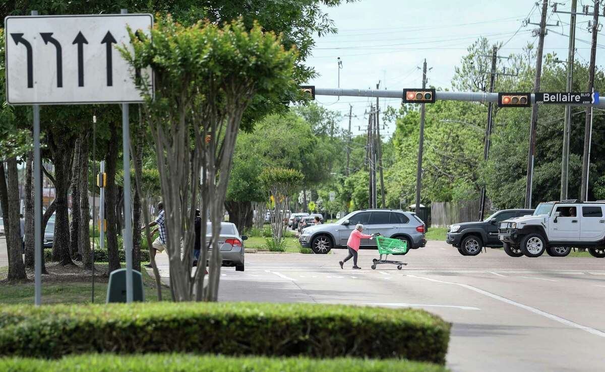 """Rosa Medrano, 71, pushes a grocery cart to a bus stop near Hillcroft Avenue and Bellaire Boulevard on April 16 in Houston. """"It's very dangerous,"""" she said in Spanish about crossing the street."""