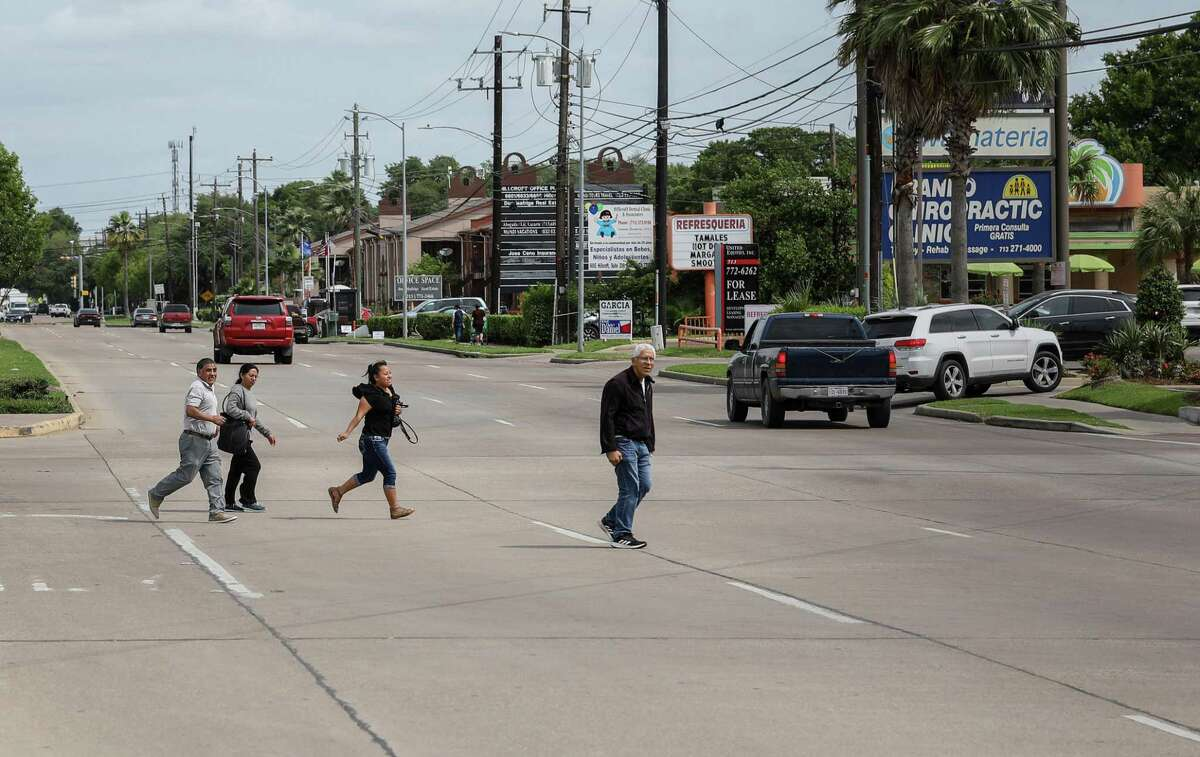 A group of people cross Hillcroft Avenue near Bellaire Boulevard on April 16 in Houston.