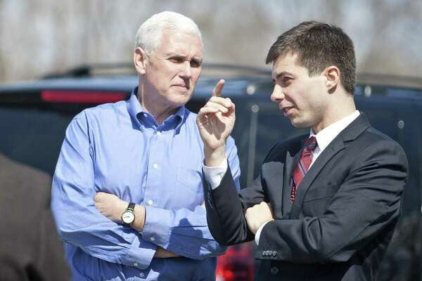 Indiana Gov. Mike Pence, left, speaks to South Bend Mayor Pete Buttigieg in 2013 following a Dyngus Day event in South Bend, Ind. Today, Democratic presidential candidate Pete Buttigieg blasts Vice President Mike Pence's religious conservatism.