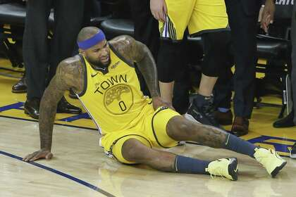 a1dac0f40ef Golden State Warriors DeMarcus Cousins lies on the floor with an apparent  injury in the first quarter during game 2 of the Western Conference  Playoffs ...