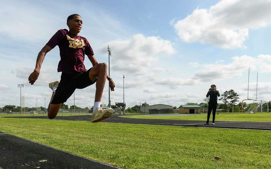 District 21-6A triple jump champion Drezden Brannon practices at Beaumont United's track on Tuesday. A'Lexus Brannon, his sister, in the background, is a former UIL state champion and is currently coaching Drezden who hopes to follow in her footsteps at Beaumont United. Photo taken on Tuesday, 04/16/19. Ryan Welch/The Enterprise Photo: Ryan Welch, The Enterprise / © 2019 Beaumont Enterprise