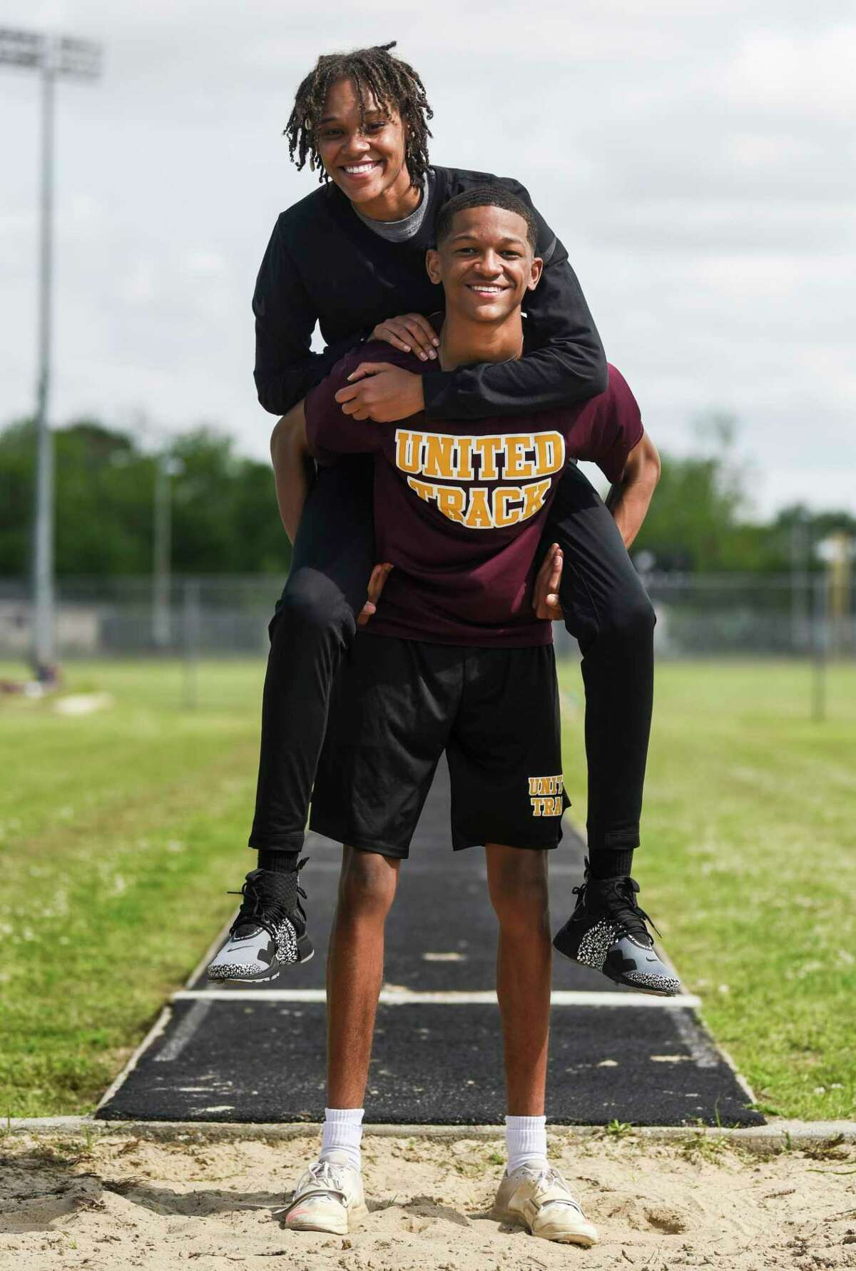 District 21-6A triple jump champion Drezden Brannon poses with his sister A'Lexus at Beaumont United's track on Tuesday. A'Lexus is a three-time consecutive UIL state championship and is currently coaching Drezden who hopes to follow in her footsteps at Beaumont United. Photo taken on Tuesday, 04/16/19. Ryan Welch/The Enterprise