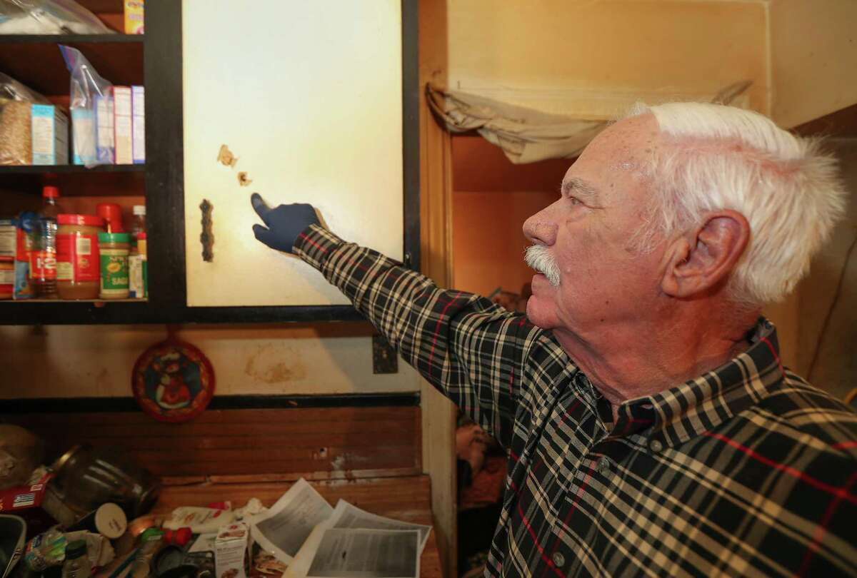 Cliff Tuttle, uncle of shooting victim Dennis Tuttle, points to several bullet holes in the kitchen as he looked inside 7815 Harding for the first time since the raid Tuesday, April 16, 2019, in Houston.