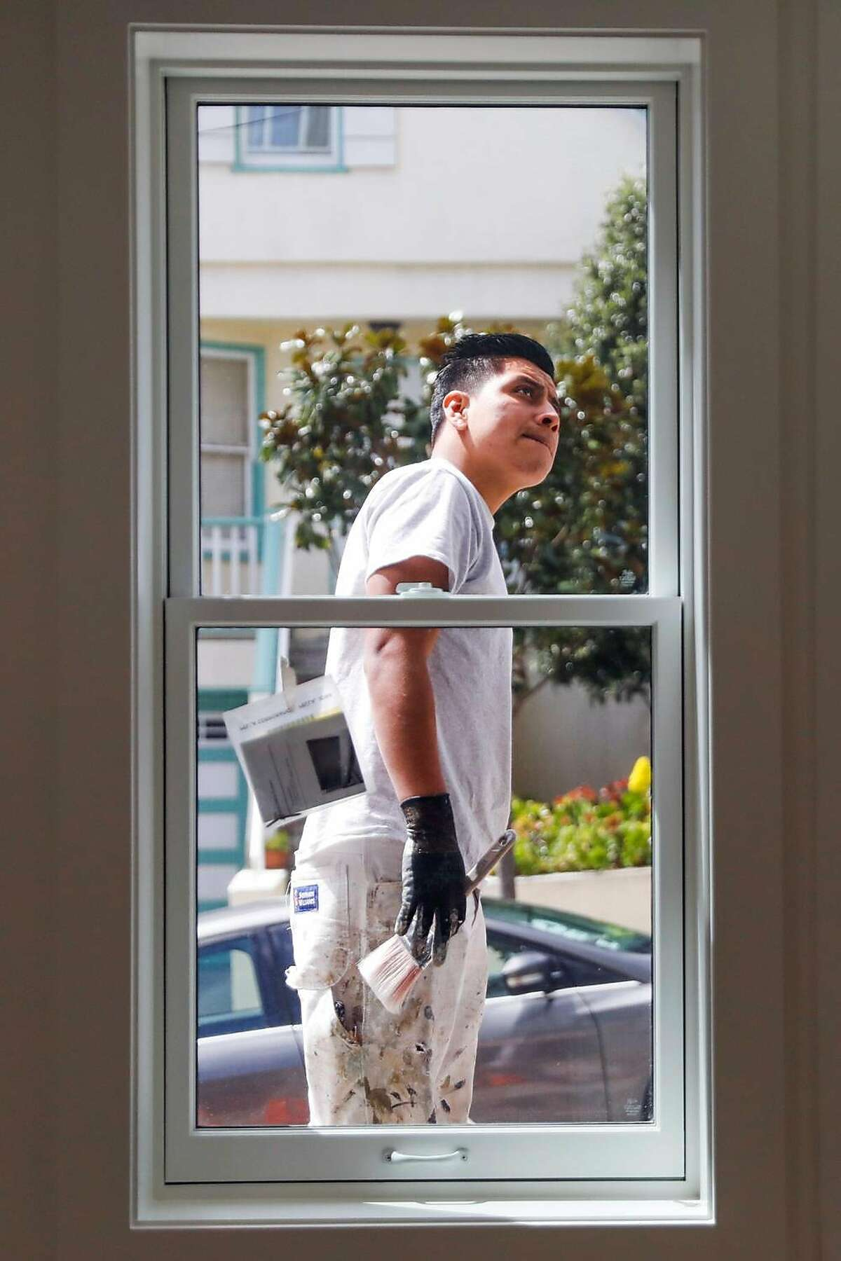 Construction worker Anelson Mejia puts the finishing touches on the exterior of an apartment that was converted from a garage into an rental unit on Roanoke Street in San Francisco.