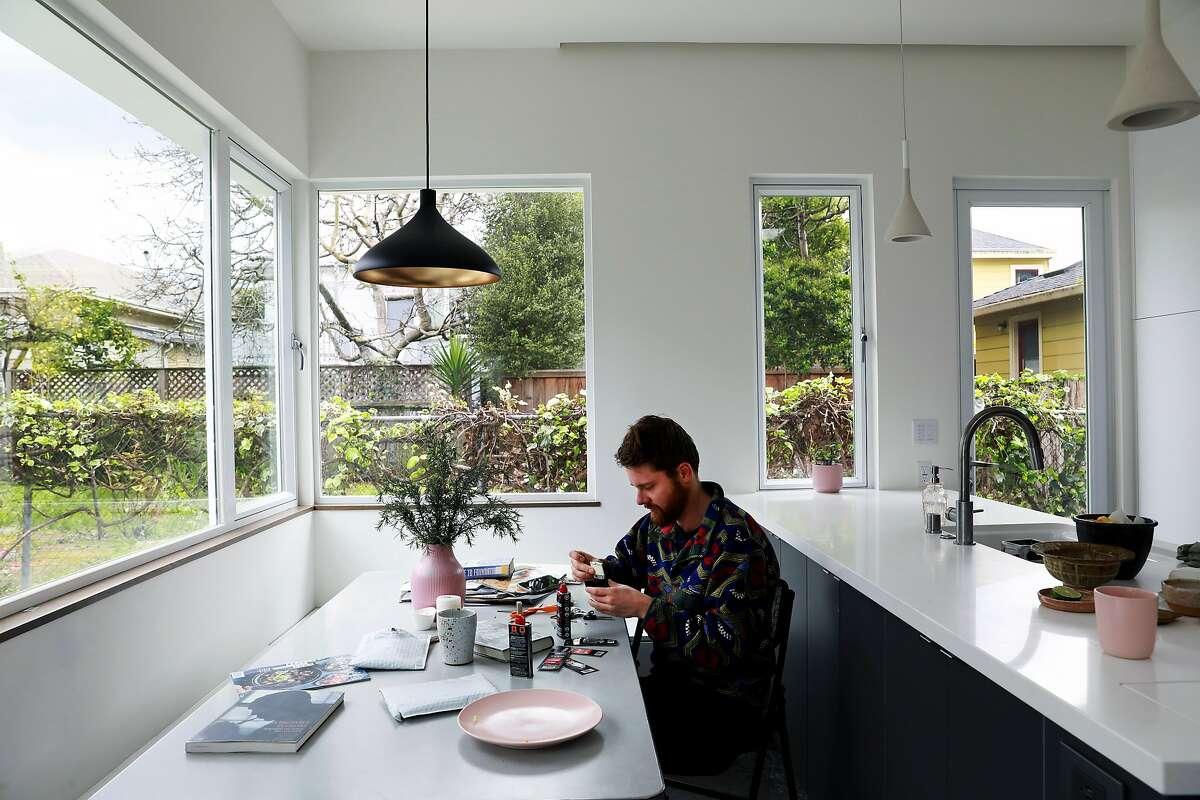 Nick Wolf works on restoring his grandmother's vintage lighters inside his 650-square foot cottage in Oakland, Calif., on Thursday, April 4, 2019. Wolf, 28, is a freelance photographer who lives in his parent's backyard.