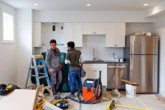 (l-r) Construction workers Robert Sanchez and Felix Guzman chat as they work on an apartment that was converted from a garage into an rental unit on Roanoke Street in San Francisco, California, on Tuesday, March 26, 2019.