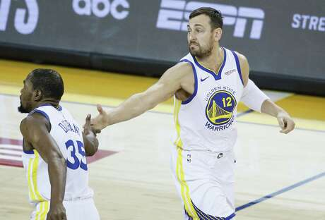 Golden State Warriors Andrew Bogut and Kevin Durant high five in the second quarter during game 1 of the Western Conference Playoffs between the Golden State Warriors and the Los Angeles Clippers at Oracle Arena on Saturday, April 13, 2019 in Oakland, Calif.