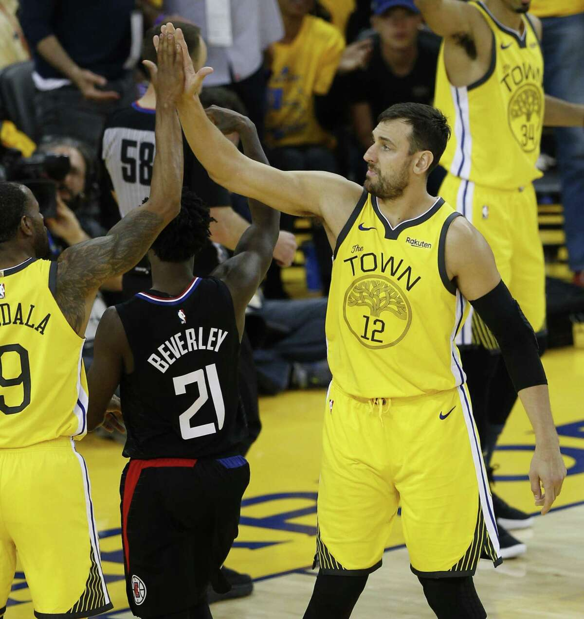 Golden State Warriors Andrew Bogut gets a high five from Andre Iguodala in the fourth quarter during game 2 of the Western Conference Playoffs between the Golden State Warriors and the Los Angeles Clippers at Oracle Arena on Monday, April 15, 2019 in Oakland, Calif.