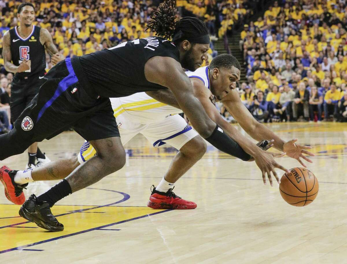 Golden State Warriors Kevon Looney and Los Angeles Clippers Montrezl Harrell chase the ball in the third quarter during game 1 of the Western Conference Playoffs between the Golden State Warriors and the Los Angeles Clippers at Oracle Arena on Saturday, April 13, 2019 in Oakland, Calif.