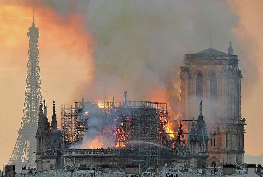 "In this image made available on Tuesday April 16, 2019 flames and smoke rise from the blaze after the spire toppled over on Notre Dame cathedral in Paris, Monday, April 15, 2019. An inferno that raged through Notre Dame Cathedral for more than 12 hours destroyed its spire and its roof but spared its twin medieval bell towers, and a frantic rescue effort saved the monument's ""most precious treasures,"" including the Crown of Thorns purportedly worn by Jesus, officials said Tuesday. (AP Photo/Thierry Mallet) Photo: Thierry Mallet / Copyright 2019 The Associated Press. All rights reserved."