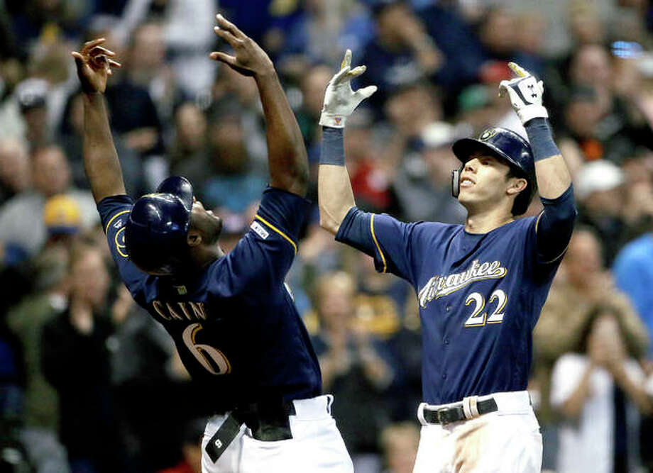 The Brewers' Christian Yelich (22) celebrates with Lorenzo Cain after hitting a three-run home run Tuesday night against the Cardinals in Milwaukee. Photo: AP Photo