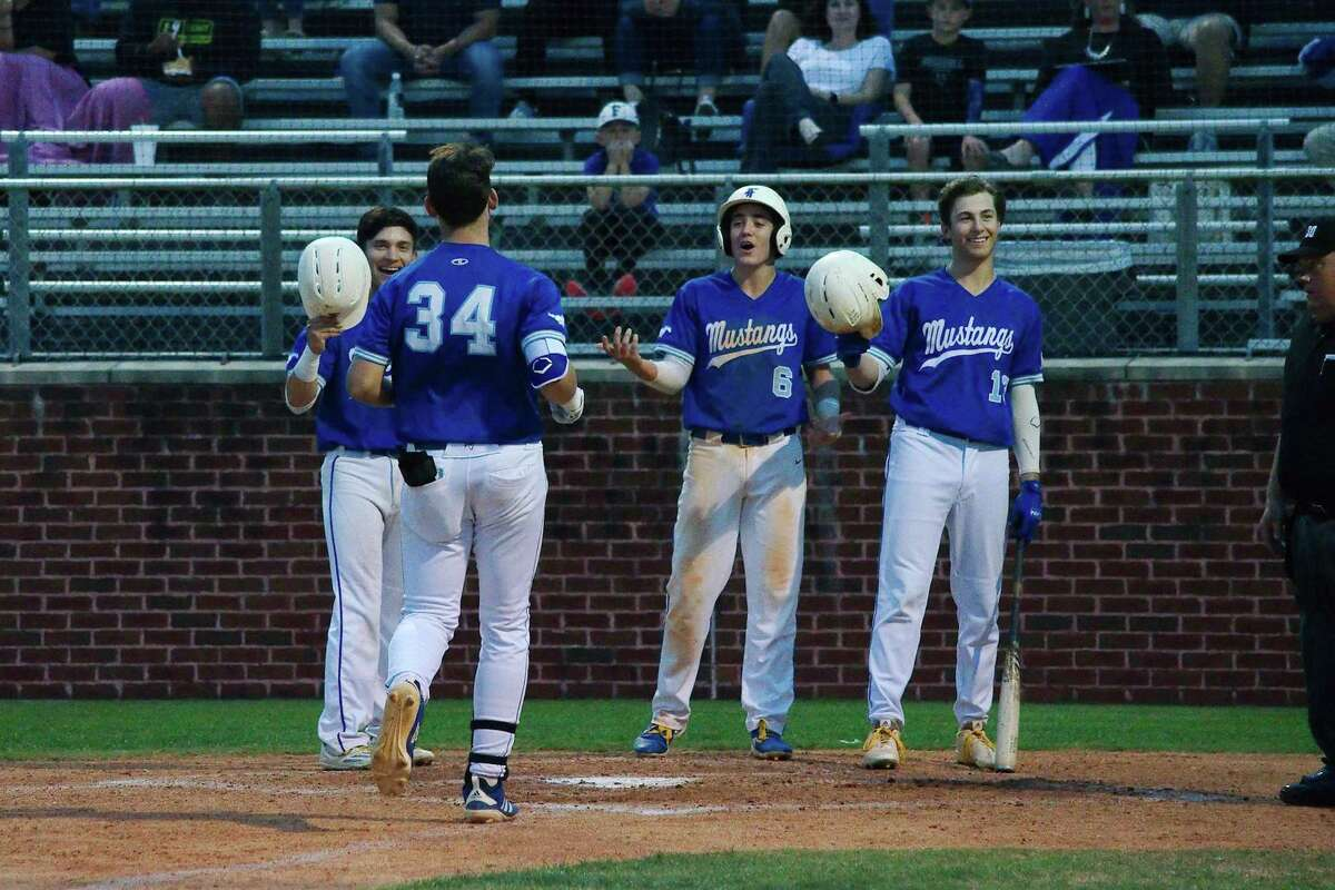 Friendswood's Isaiah Winkler (23), Devon Andrews (6) and Kevin Newkirk (13) congratulate Izaac Pacheco (34) after his home run against Galveston Ball Tuesday night.