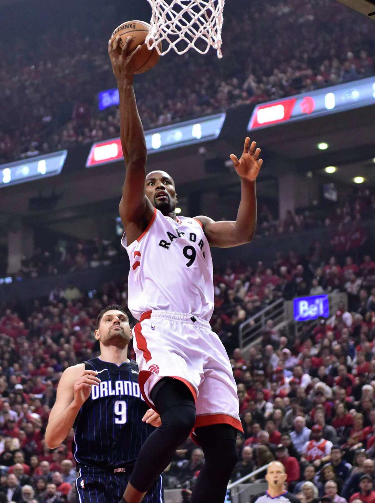 Toronto Raptors' Serge Ibaka scores as Orlando Magic centre Nikola Vucevic (9) watches during the first half of Game 2 of an NBA basketball first-round playoff series Tuesday, April 16, 2019, in Toronto. (Frank Gunn/The Canadian Press via AP)