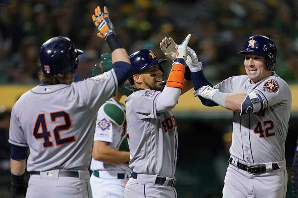 OAKLAND, CA - APRIL 16: (R-L) Alex Bregman #2, Robinson Chirinos #28 and Josh Reddick #22 of the Houston Astros celebrates after Bregman hit a grand slam home run against the Oakland Athletics in the top of the fourth inning of a Major League Baseball game at Oakland-Alameda County Coliseum on April 16, 2019 in Oakland, California. All uniformed players and coaches are wearing number 42 in honor of Jackie Robinson Day.