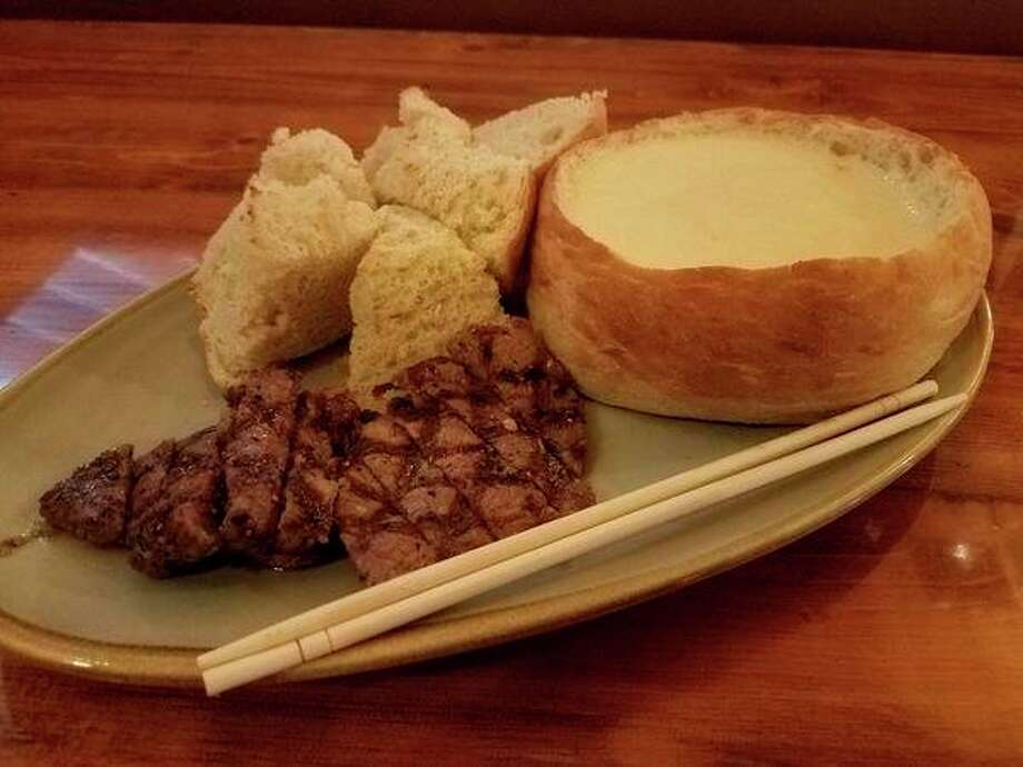 Steak fondue -- a bread bowl brimming with golden cheese with sliced steak bits and thick chunks of chewy bread -- at Timbers Bar & Grill, located at 6415 State Street in Saginaw, just off of M-47. (Matthew Woods | for the Daily News)