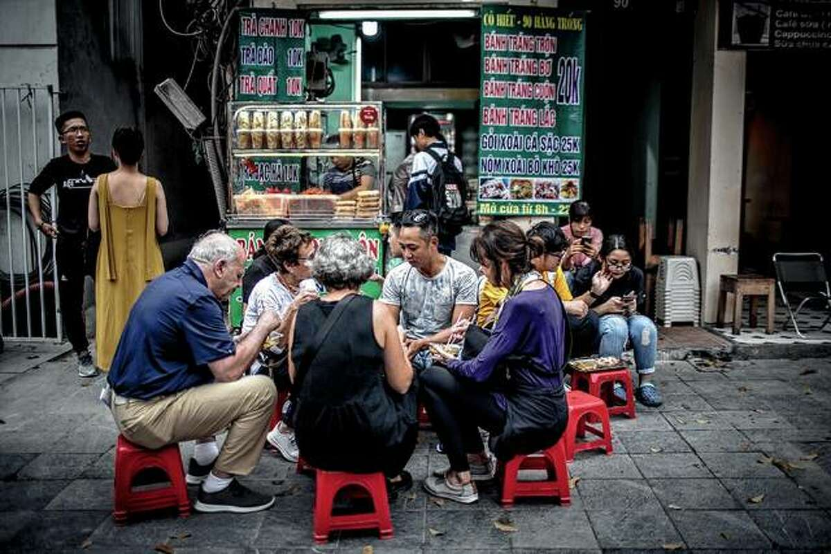 A group eats in March on a stop during a trip organized by Hanoi Street Food Tours in Hanoi, Vietnam.