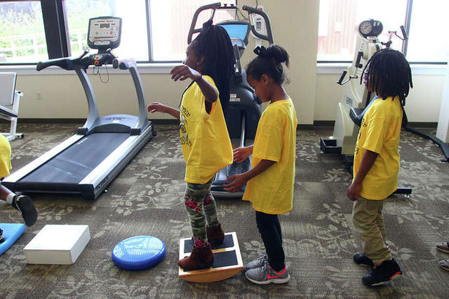 Lincoln Elementary School students Semajah Sanders, Sincere Day-Powell and Gerald Jackson test their balance in the rehabilitation department at Passavant Area Hospital during the Mini-Medical Days tour Tuesday. For more photos from Mini-Medical Days, visit myjournalcourier.com