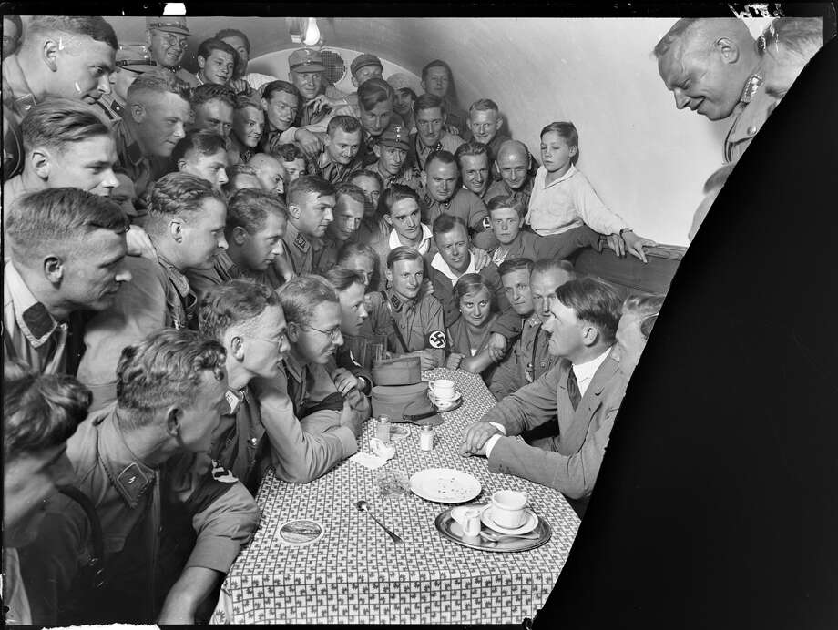 Adolph Hitler, seated at right, with group of admirers in a café. The National Archives is digitizing about 1,300 images from glass photo negatives created by Hitler's personal photographer Heinrich Hoffmann. Photo: National Archives And Records Administration. / National Archives and Records Administration