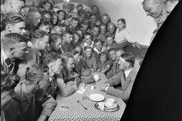 Adolph Hitler, seated at right, with group of admirers in a café. The National Archives is digitizing about 1,300 images from glass photo negatives created by Hitler's personal photographer Heinrich Hoffmann.