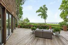 The large, inviting deck of this Darien home overlooks Long Island Sound, making it the ideal spot for outdoor activity. Below, a stylish pergola caps off a patio, filtering the sun.