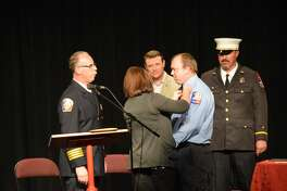 As the firefighters were honored, loved ones presented them with pins for their uniforms