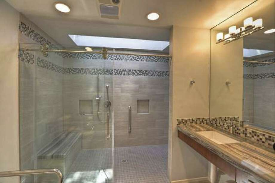 This shower features a curbless entry, built-in bench and grab bars.
