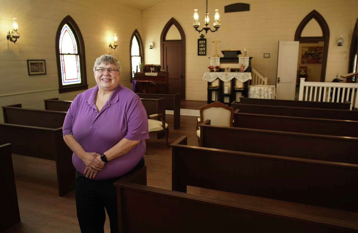 Rev. Vicki Sheil-Hopper in St. Peter's historic chapel. Some of the pews, like the building, date back to 1864.