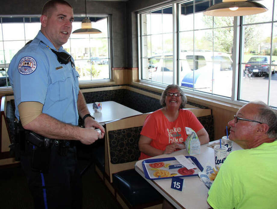 Edwardsville Police Officer Wesley Nolden explains to Deb and Gary Heidemann why he brought their dinners instead of a Culver's employee during ButterBurgers and Badges Tuesday. Photo: Charles Bolinger | The Intelligencer