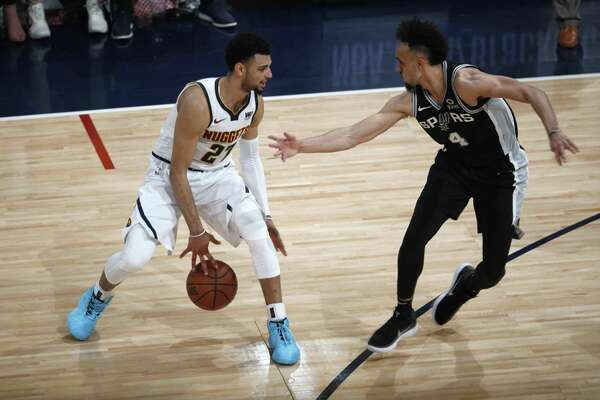 Denver Nuggets guard Jamal Murray, left, looks to shoot the ball as San Antonio Spurs guard Derrick White defends in the second half of Game 2 of an NBA basketball playoff series Tuesday, April 16, 2019, in Denver. The Nuggets won 114-105. (AP Photo/David Zalubowski)