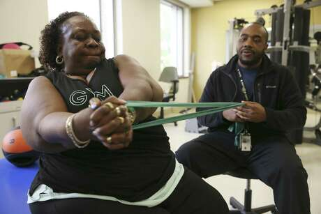 Disabled army vet Phyllis Jarman, 63, works with kinesiotherapist Derrick Mason at the Weight and Metabolic Disorder Treatment Center (WAMD) at Audie L. Murphy Memorial VA Hospital. The program takes a team approach to treat obesity, diabetes and related diseases in military veterans.