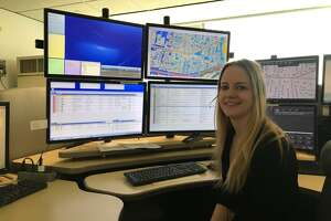 Stamford 911 Telecommunicator of the Year, Erin Walsh, 31, sitting at her cubicle in the 911 Dispatch Center at Government Center.