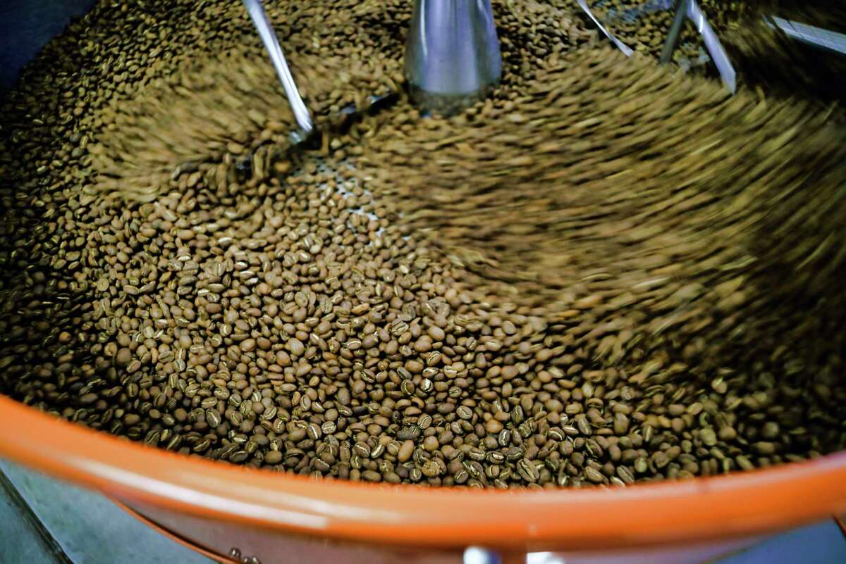 Just roasted coffee beans are pushed around in a bin after coming out of the drum coffee roaster at Brewtus Roasting on Monday, April 15, 2019, in Delmar, N.Y. (Paul Buckowski/Times Union)