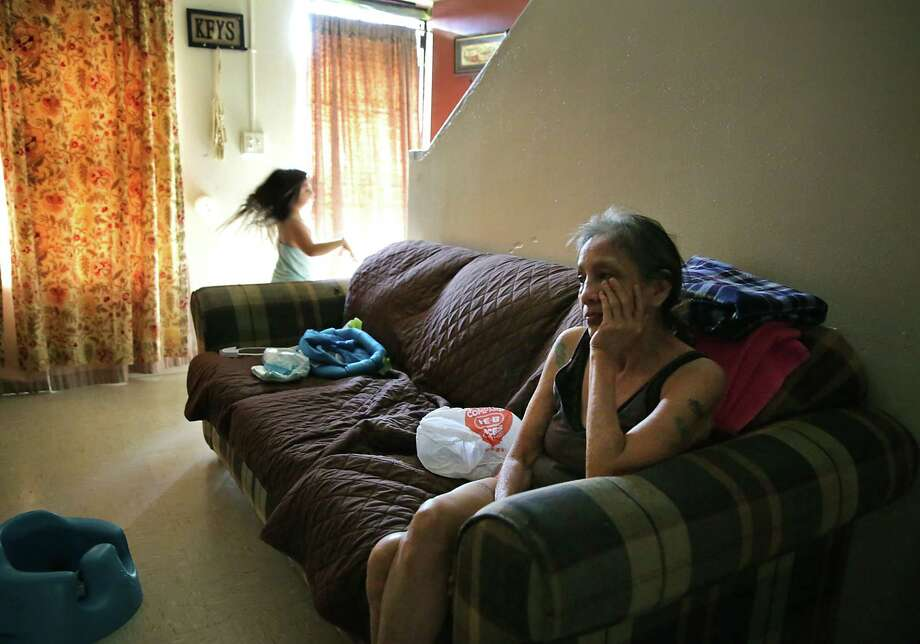 Cathy Galindo, 60, sits on her sofa as her great-granddaughter Nevaeh, 5, plays in her Alazan-Apache Courts apartment, which doesn't have air conditioning. There's no law that requires landlords, including local housing authorities managing government-subsidized housing, to provide air conditioners. Photo: Bob Owen / ©2019 San Antonio Express-News