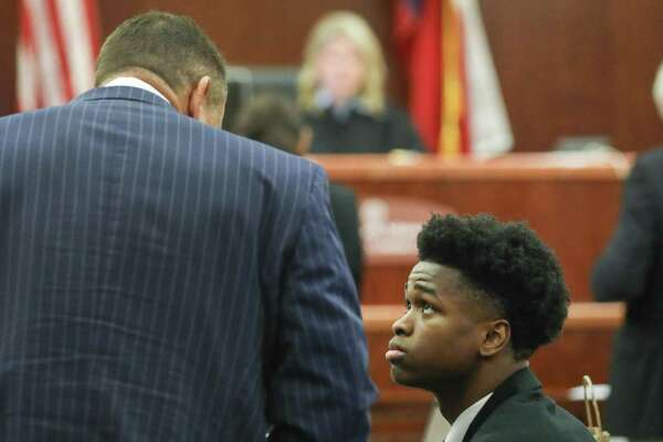 Antonio Armstrong, Jr., right, talks with his attorney Chris Collings while on break in the capital murder trial for the deaths of his parents, on Tuesday, April 9, 2019, in Houston.