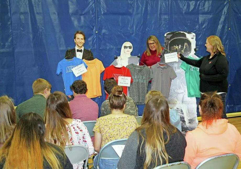Tracy Talaski, left, and Jena Zimmerman, both of Northstar Bank, hosted a clothing budget station. Here, students were able to choose whether they wanted to purchase their wardrobe from high end retailers, discount retailers, or thrift stores. (Seth Stapleton/Huron Daily Tribune)