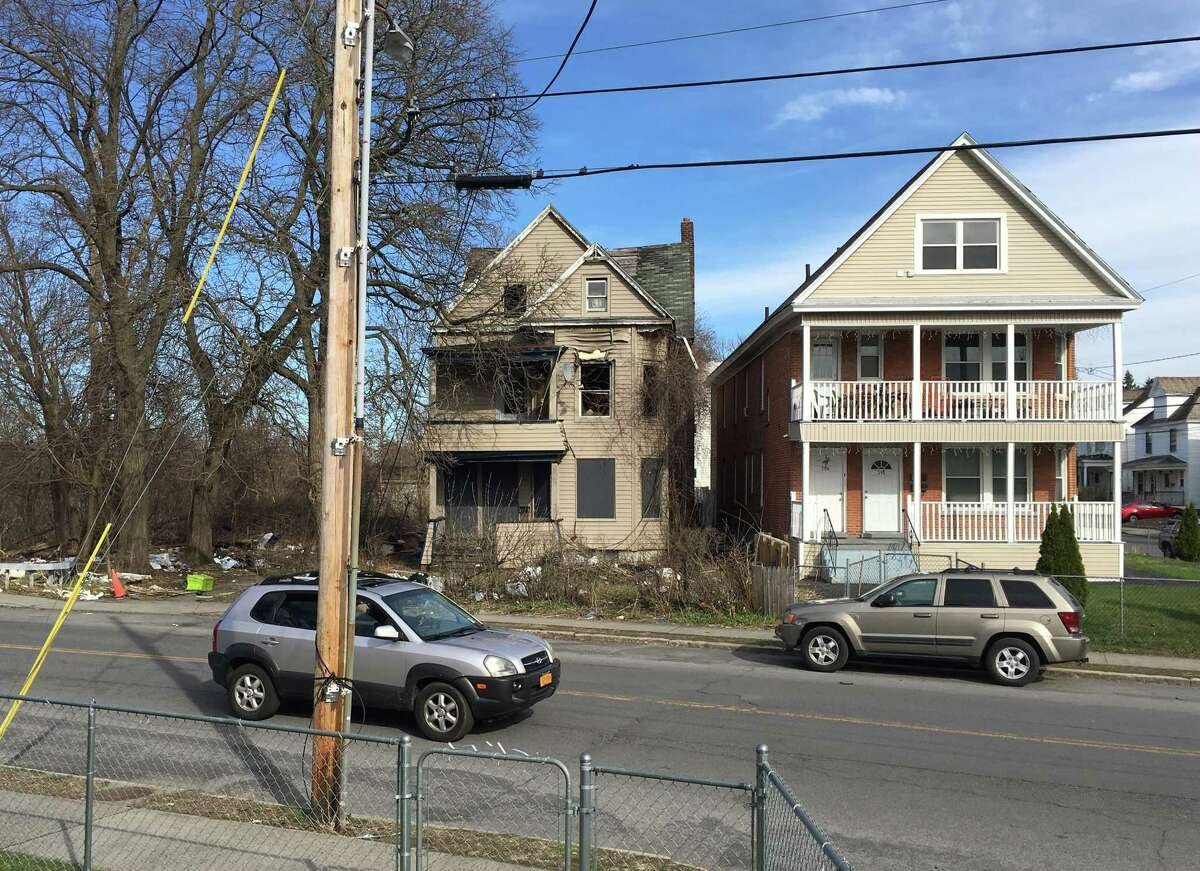 This city-owned property at 792 Francis Avenue, left, is strewn with trash on Wednesday, April 17, 2019, in Schenectady, N.Y. Neighbors are upset with the ill-kept eyesore. The city owns the property after taking it in a tax foreclosure in 2017. (Paul Nelson/Times Union)