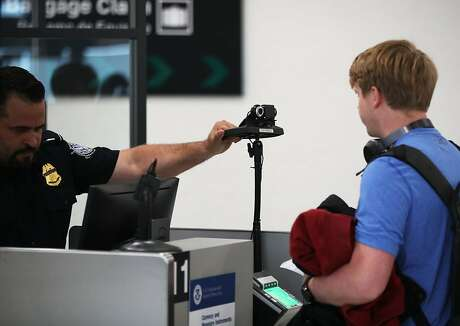 A U.S. Customs and Border Protection officer instructs an international traveler to look into a camera as he uses facial recognition technology to screen a traveler entering the United States on February 27, 2018 at Miami International Airport in Miami, Florida. (Joe Raedle/Getty Images/TNS) *FOR USE WITH THIS STORY ONLY*
